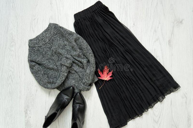 Γκρίζο θερμό πουλόβερ, μαύρες φούστα και μπότες μοντέρνη έννοια στοκ φωτογραφία