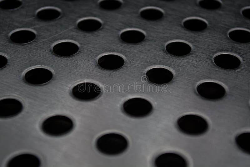 Γκρίζο μονοφωνικό υπόβαθρο με τη μεγάλη ποσότητα τρυπών σε ένα μεταλλικό πιάτο Επιφάνεια r στοκ εικόνες