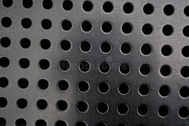 Γκρίζο μονοφωνικό υπόβαθρο με τη μεγάλη ποσότητα τρυπών σε ένα μεταλλικό πιάτο Επιφάνεια r στοκ φωτογραφίες με δικαίωμα ελεύθερης χρήσης