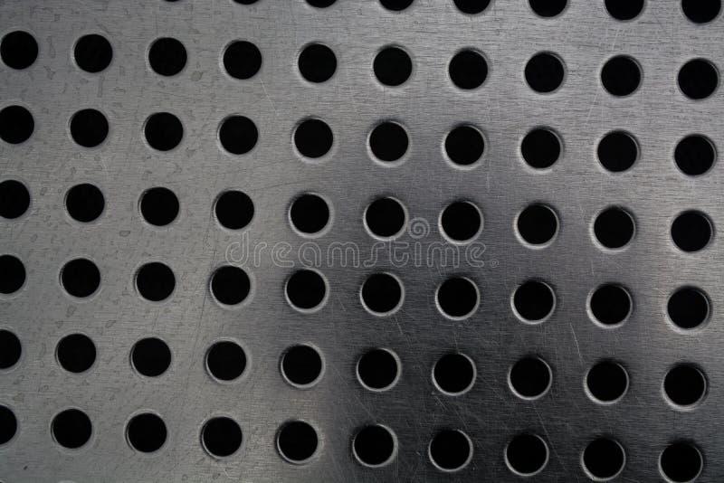 Γκρίζο μονοφωνικό υπόβαθρο με τη μεγάλη ποσότητα τρυπών σε ένα μεταλλικό πιάτο Επιφάνεια r στοκ φωτογραφία