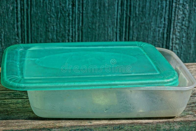 Γκρίζο πράσινο πλαστικό κενό κιβώτιο τροφίμων στον ξύλινο πίνακα στοκ εικόνες