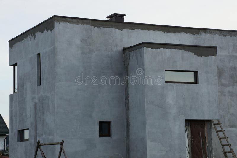 Γκρίζο συγκεκριμένο ατελές σπίτι με τα μικρά παράθυρα στοκ εικόνες