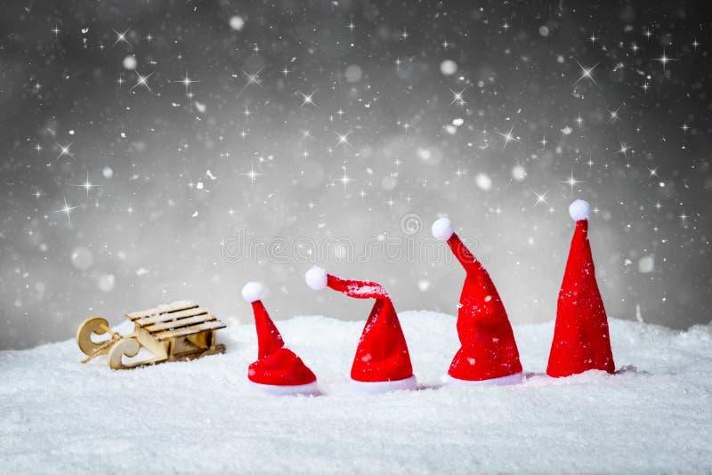 Γκρίζο υπόβαθρο Χριστουγέννων με τα καπέλα Santa και έλκηθρο στο χιόνι στοκ φωτογραφίες