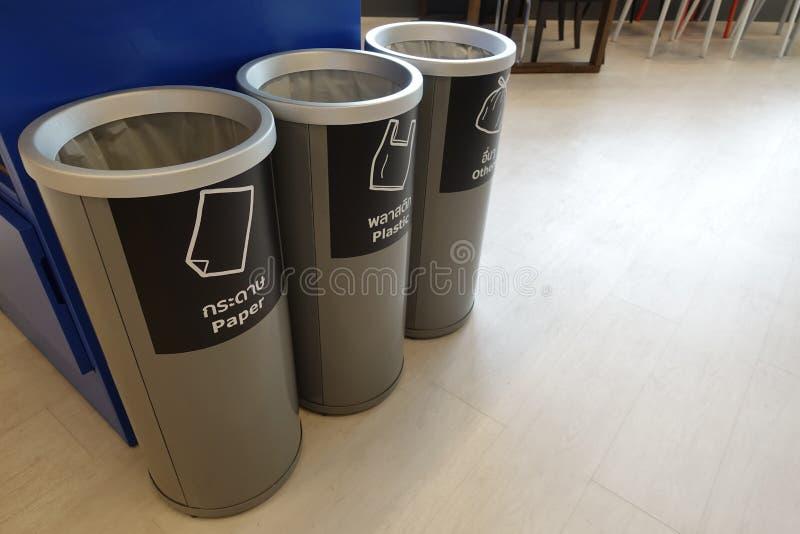 Γκρίζο χωριστό πλαστικό εμπορευματοκιβώτιο τρία, τα οποία ανακυκλώνουν τα σύμβολα που σφραγίζονται σε χαρτί, τα πλαστικά, και άλλ στοκ φωτογραφία με δικαίωμα ελεύθερης χρήσης