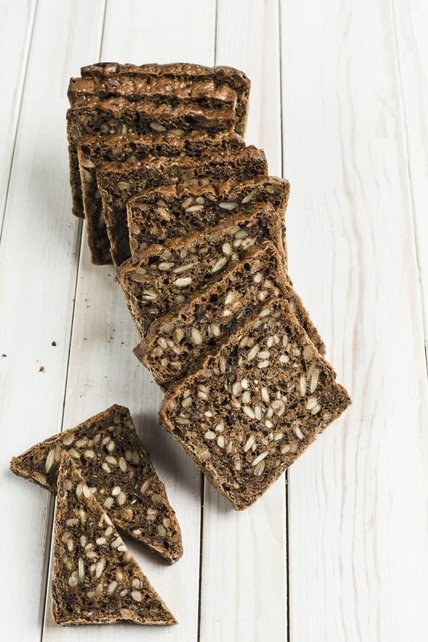Γλουτένη-ελεύθερο ψωμί με τους σπόρους φουντουκιών και λιναριού σε έναν ξύλινο πίνακα στοκ εικόνες