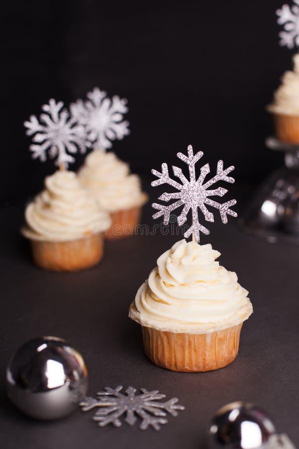 Γλυκά για τα Χριστούγεννα - Χριστούγεννα cupcake με το τυρί κρέμας που διακοσμείται με λάμποντας ασημένια snowflakes στο μαύρο υπ στοκ φωτογραφίες