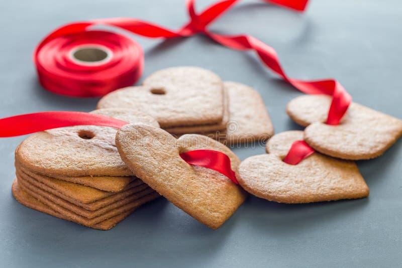 Γλυκά διακοπών Σουηδικό pepparkakor μπισκότων μελοψωμάτων Χριστουγέννων, που διακοσμείται με μια κόκκινη κορδέλλα, σε ένα σκούρο  στοκ φωτογραφία με δικαίωμα ελεύθερης χρήσης