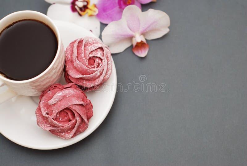 Γλυκά ρόδινα μαρέγκες και φλιτζάνι του καφέ στο μπλε γκρίζο υπόβαθρο με τα λουλούδια ορχιδεών Υπόβαθρο άνοιξη με το διάστημα αντι στοκ εικόνες