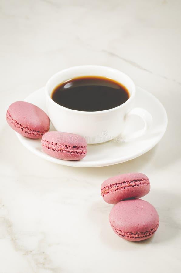 γλυκά macaroons ή macaron και άσπρο φλυτζάνι καφέ σε ένα άσπρο υπόβαθρο, γαλλικό επιδόρπιο στοκ εικόνες με δικαίωμα ελεύθερης χρήσης