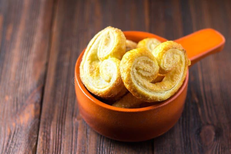 Γλυκά pretzels φιαγμένα από ζύμη ριπών σε ένα κύπελλο σε έναν ξύλινο πίνακα στοκ εικόνες