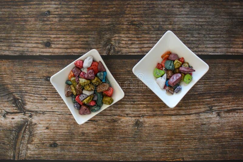 Γλυκές ζωηρόχρωμες καραμέλες σοκολάτας, στα μικρά άσπρα κύπελλα, στο σκοτεινό ξύλινο υπόβαθρο στοκ φωτογραφίες με δικαίωμα ελεύθερης χρήσης