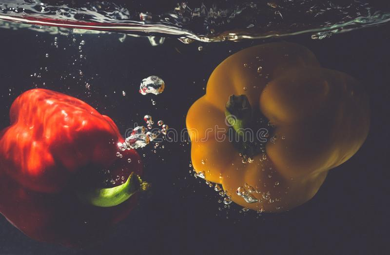 Γλυκές πτώσεις κόκκινων πιπεριών στο νερό με το ράντισμα στοκ φωτογραφίες με δικαίωμα ελεύθερης χρήσης