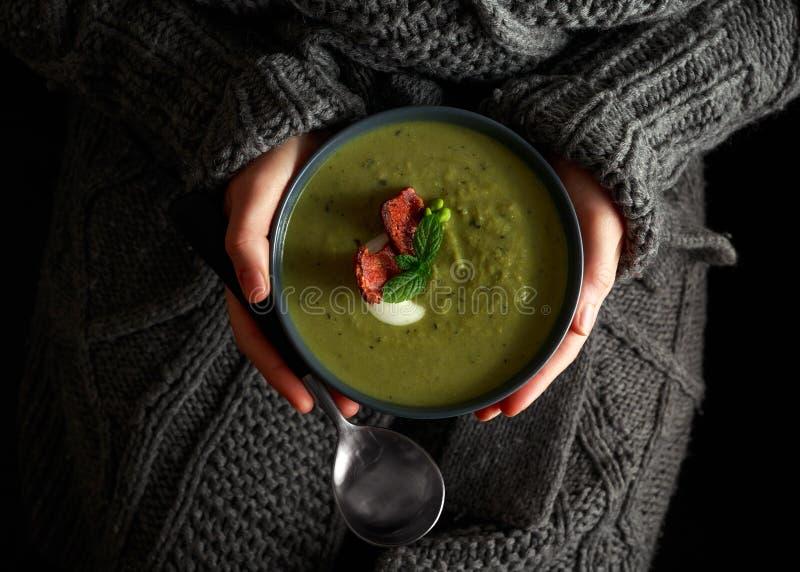 Γλυκιά καυτή σούπα μπιζελιών, πράσων και μεντών που ολοκληρώνεται με το τραγανό μπέϊκον και dolop του γιαουρτιού Παραδίδει το που στοκ εικόνες
