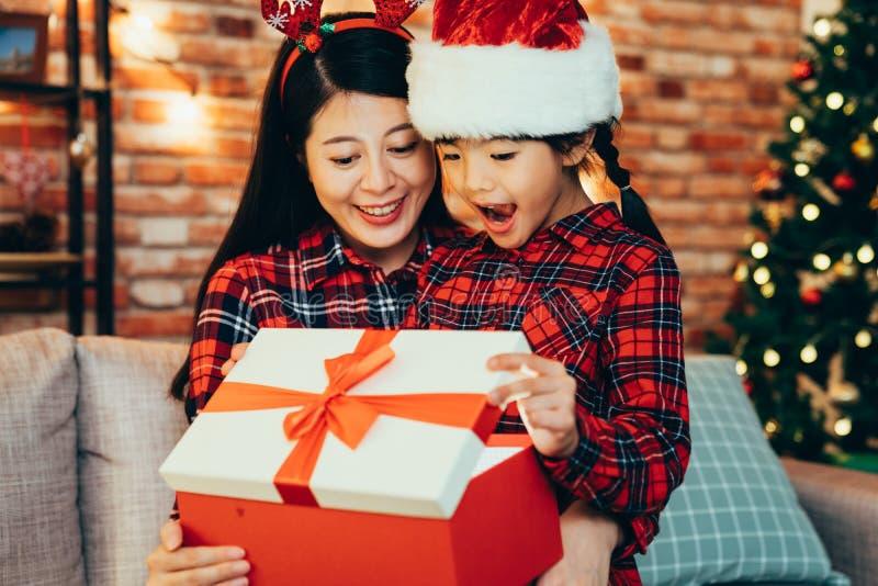 Γλυκιά οικογένεια που ανοίγει το μεγάλο κιβώτιο δώρων στη επόμενη μέρα των Χριστουγέννων στοκ φωτογραφίες