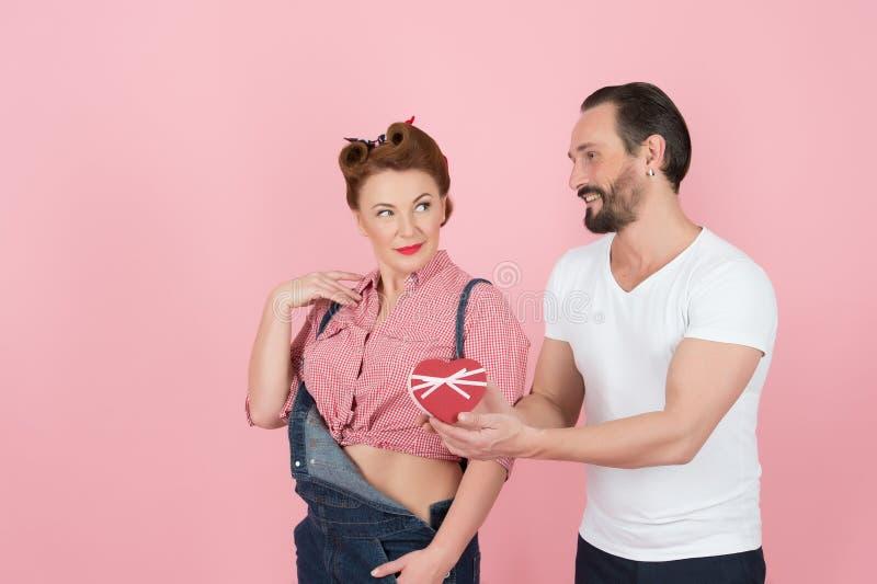 Γλυκό ζεύγος που επιλέγει την καρδιά Άνδρας στην άσπρη μπλούζα που παρουσιάζει την καρδιά του στη γυναίκα brunette στο τζιν Ο τύπ στοκ εικόνες