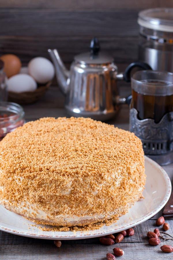 Γλυκό κατ' οίκον βαλμένο σε στρώσεις κέικ μελιού σε έναν ξύλινο πίνακα με τα καρύδια στοκ φωτογραφίες