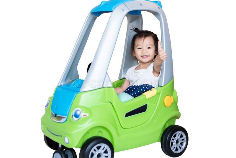Γλυκό λίγο ασιατικό κορίτσι που οδηγά στο μικρό αυτοκίνητο με τον αντίχειρα που απομονώνεται επάνω στο λευκό στοκ φωτογραφία με δικαίωμα ελεύθερης χρήσης