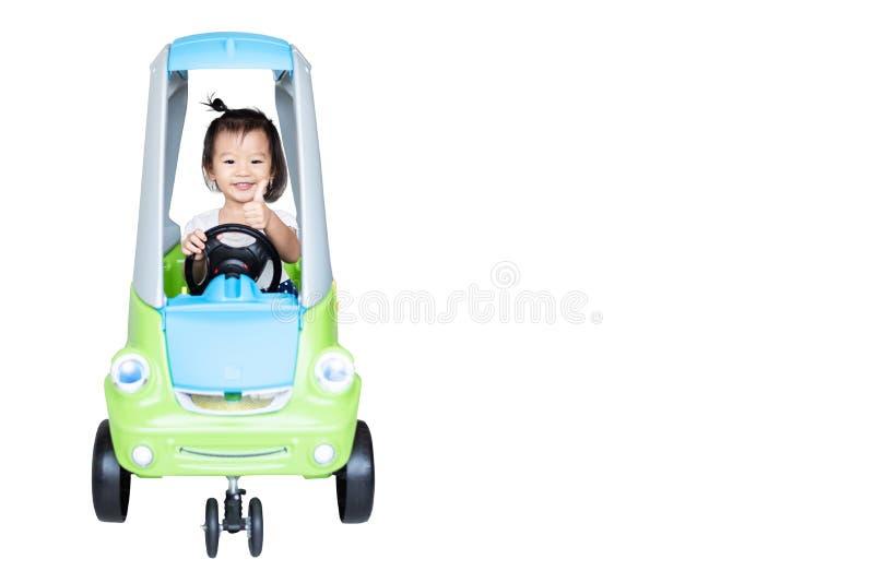 Γλυκό λίγο ασιατικό κορίτσι που οδηγά στο μικρό αυτοκίνητο που απομονώνεται στο λευκό στοκ εικόνες