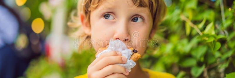 Γλυκό λίγο καυκάσιο αγόρι, που τρώει τις τηγανίτες και που πίνει το ΕΜΒΛΗΜΑ χυμού από πορτοκάλι, ΜΑΚΡΟΧΡΟΝΙΟ ΣΧΗΜΑ στοκ φωτογραφία με δικαίωμα ελεύθερης χρήσης