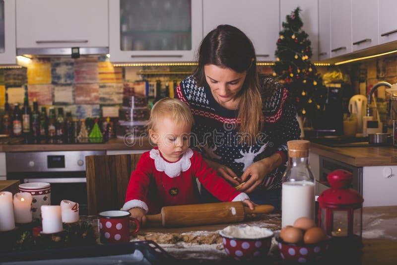 Γλυκό παιδί μικρών παιδιών, αγόρι, που βοηθά τη μαμά που προετοιμάζει το μάγειρα Χριστουγέννων στοκ εικόνα με δικαίωμα ελεύθερης χρήσης