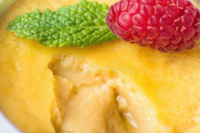 Γλυκό Flan κρέμας κρέμας αυγών βανίλιας με το φρέσκο σμέουρο και μέντα στο φλυτζάνι μερίδας που εκσκάπτεται Μακρο φωτογραφία τροφ στοκ εικόνες