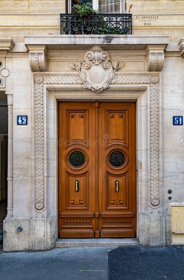 Γλυπτική αψίδα εισόδων και παλαιά διπλή πόρτα με τα στρογγυλά πλαισιωμένα παράθυρα πορτών του παλαιού κτηρίου στο Παρίσι Γαλλία Ε στοκ εικόνες