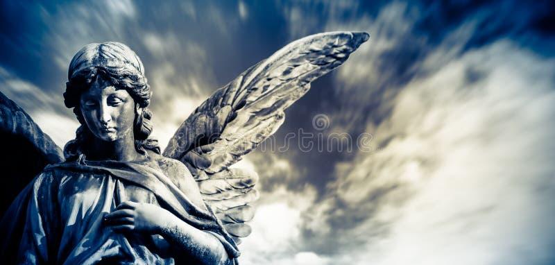 Γλυπτό αγγέλου φυλάκων με τα ανοικτά μακριά φτερά με το θολωμένο άσπρο δραματικό ανοικτό μπλε ουρανό σύννεφων Λυπημένη έκφραση αγ στοκ εικόνα