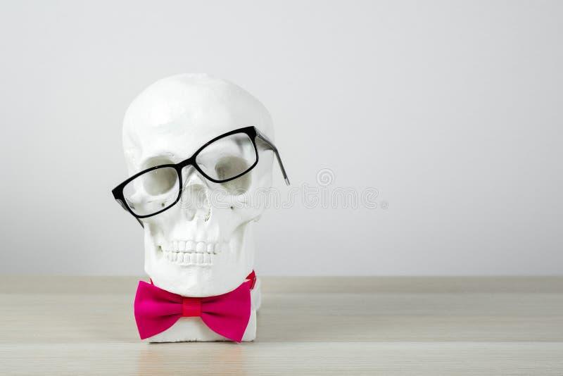 Γλυπτό κρανίων στα συγκλονισμένα μαύρα γυαλιά και ένας ρόδινος δεσμός τόξων, αποτυχία, γλυπτό στο ελαφρύ υπόβαθρο στον πίνακα Bac στοκ φωτογραφία