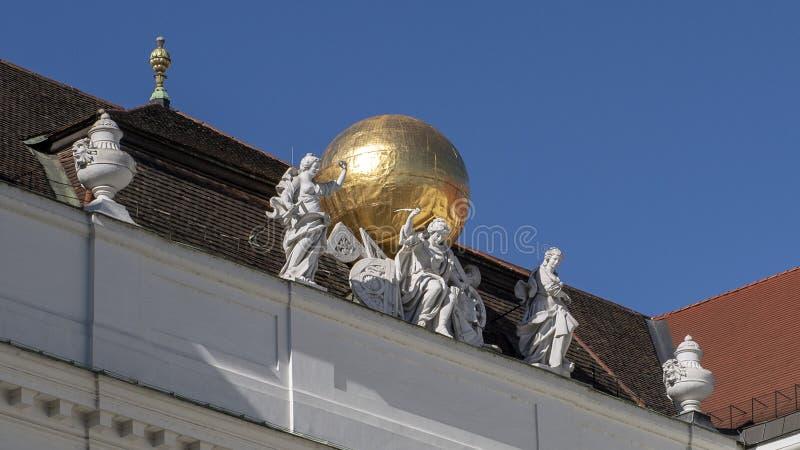 Γλυπτό με τη χρυσή σφαίρα επάνω στην κρατική αίθουσα της αυστριακής εθνικής βιβλιοθήκης, που βλέπει από Josefsplatz στοκ εικόνα