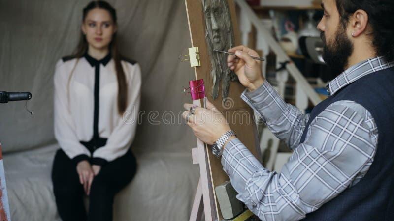 Γλύπτης που δημιουργεί το γλυπτό του ανθρώπινου προσώπου ` s στον καμβά ενώ νέα γυναίκα που θέτει τον στο στούντιο τέχνης στοκ εικόνα με δικαίωμα ελεύθερης χρήσης