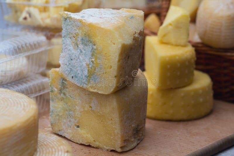 Γνήσιο τυρί κομματιών περικοπών με μια φόρμα, κατάταξη στην αγορά αγροτών στοκ φωτογραφία με δικαίωμα ελεύθερης χρήσης