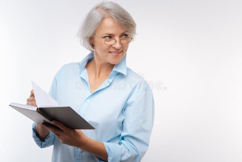 Γοητεία της ανώτερης γυναίκας που διαβάζει ένα βιβλίο στοκ εικόνες