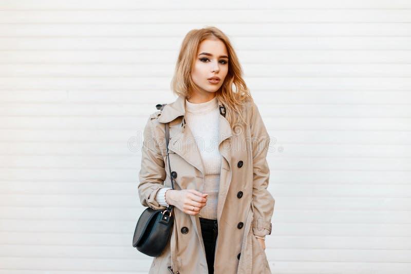 Γοητεία της μοντέρνης νέας γυναίκας στο καθιερώνον τη μόδα παλτό άνοιξη στην άσπρη μπλούζα με τη μαύρη μοντέρνη τσάντα δέρματος στοκ εικόνα