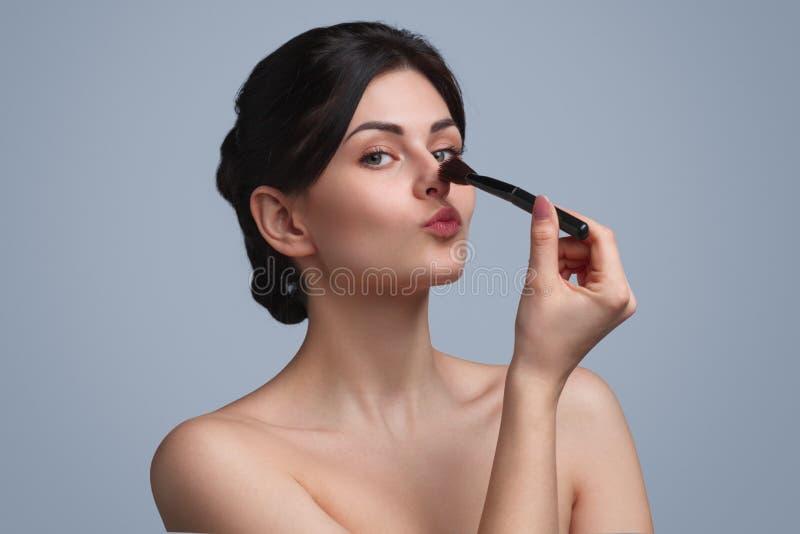 Γοητεία της νέας γυναίκας με την καλλυντική βούρτσα στοκ φωτογραφίες