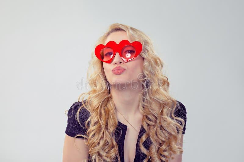 Γοητεία της ξανθής γυναίκας στα καρδιά-διαμορφωμένα γυαλιά στοκ εικόνες