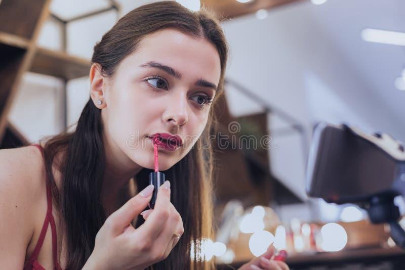 Γοητεία της σκοτεινός-μαλλιαρής γυναίκας που χρωματίζει τα χείλια της στοκ εικόνες