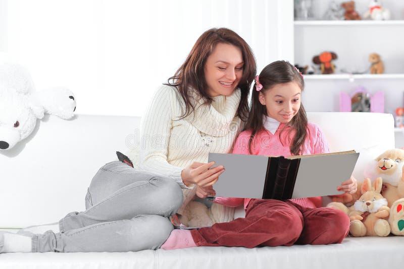 Γοητευτικές μητέρα και κόρη που διαβάζουν μια συνεδρίαση βιβλίων στον καναπέ Φωτογραφία με το διάστημα αντιγράφων στοκ φωτογραφίες με δικαίωμα ελεύθερης χρήσης