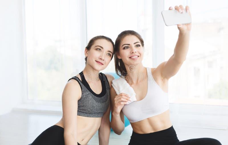 Γοητευτικές φίλες που κάνουν selfie μετά από την κατηγορία γιόγκας στοκ εικόνες