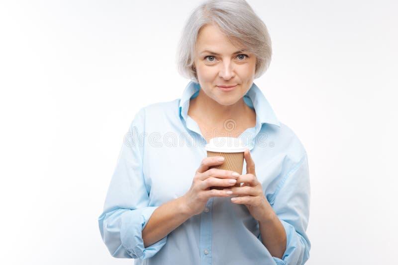 Γοητευτική γκρίζος-μαλλιαρή τοποθέτηση γυναικών με το φλυτζάνι καφέ στοκ εικόνες