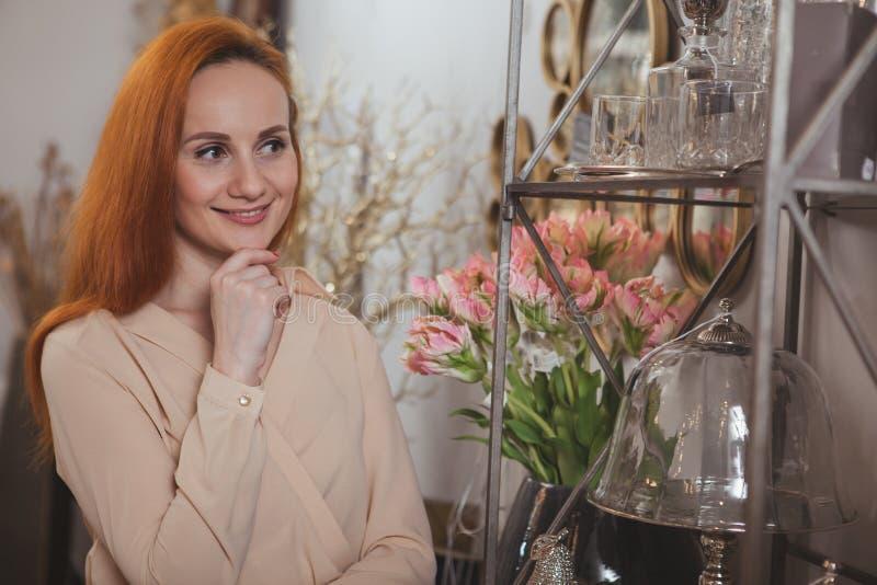 Γοητευτική γυναίκα που απολαμβάνει στο σπίτι το κατάστημα ντεκόρ στοκ εικόνα με δικαίωμα ελεύθερης χρήσης