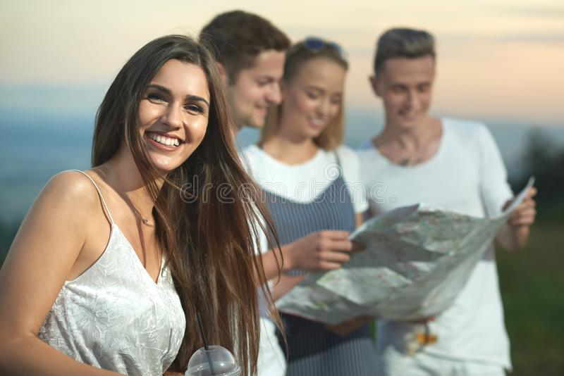 Γοητευτική γυναίκα που χαμογελά και που εξετάζει τη κάμερα ενώ φίλοι που κρατούν το χάρτη στοκ φωτογραφία με δικαίωμα ελεύθερης χρήσης