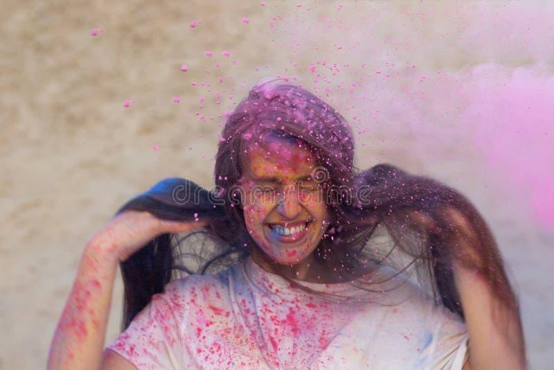 Γοητευτική γυναίκα brunette με το μακρυμάλλες παιχνίδι με τη ρόδινη ξηρά σκόνη Holi στην έρημο στοκ φωτογραφία με δικαίωμα ελεύθερης χρήσης