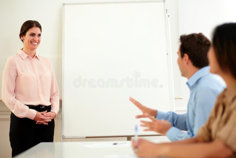 Γοητευτική επιχειρηματίας που χαμογελά στους συναδέλφους της στοκ φωτογραφία με δικαίωμα ελεύθερης χρήσης