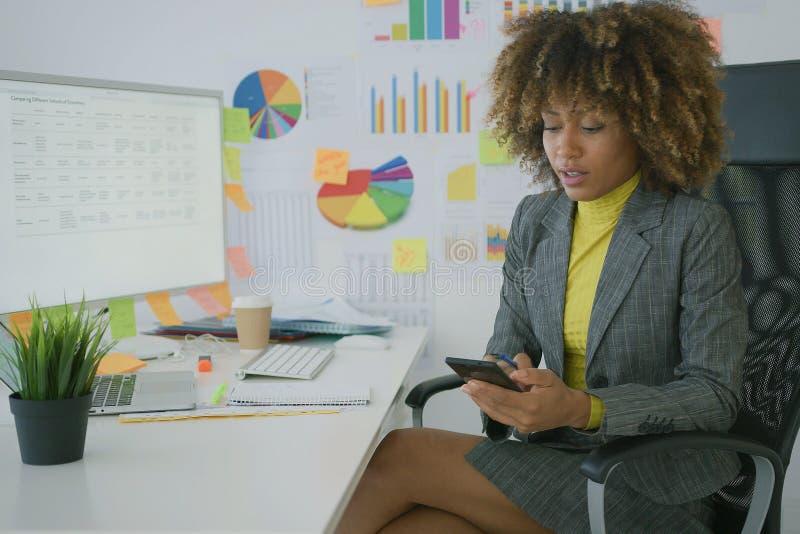 Γοητευτική επιχειρηματίας που χρησιμοποιεί το τηλέφωνο στον εργασιακό χώρο στοκ εικόνες