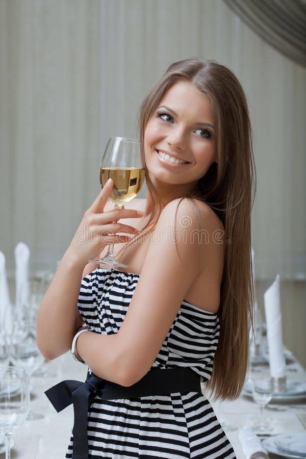 Γοητευτική τοποθέτηση κοριτσιών χαμόγελου με το ποτήρι του κρασιού στοκ φωτογραφίες με δικαίωμα ελεύθερης χρήσης