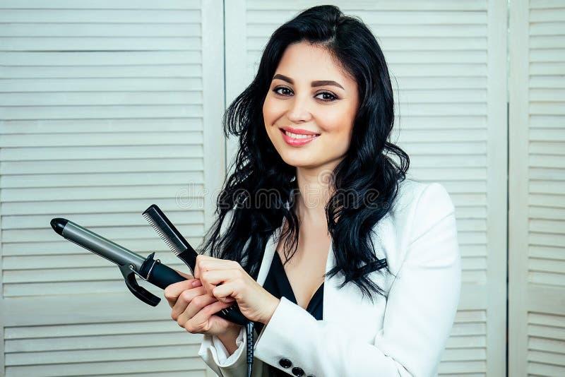 Γοητευτική όμορφη γυναίκα κομμώτρια στυλίστας που κάνει κομμωτικό στυλ και κρατά στο χέρι κιμά σίδερο στο σαλόνι στοκ εικόνες με δικαίωμα ελεύθερης χρήσης