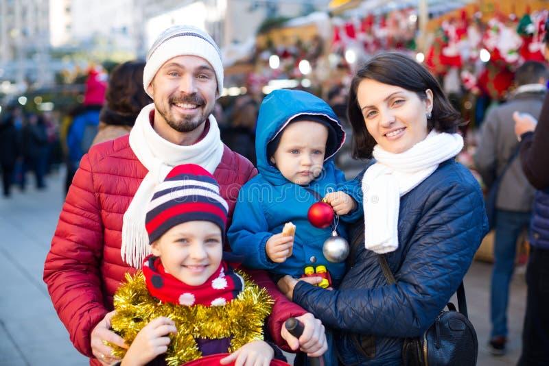 Γοητευτικοί γονείς με τα παιδιά που επιλέγουν τις διακοσμήσεις διακοπών στοκ φωτογραφία με δικαίωμα ελεύθερης χρήσης