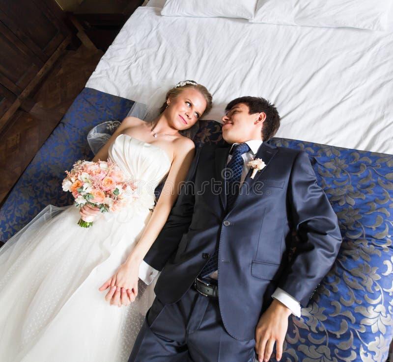 Γοητευτικοί νύφη και νεόνυμφος στην κρεβατοκάμαρά τους στοκ εικόνα