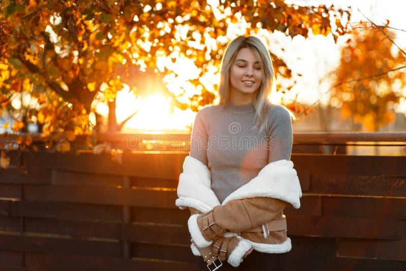 Γοητευτικός την ευτυχή νέα γυναίκα σε έναν γκρίζο καθιερώνοντα τη μόδα τρύγο πλεκτό στοκ εικόνα με δικαίωμα ελεύθερης χρήσης