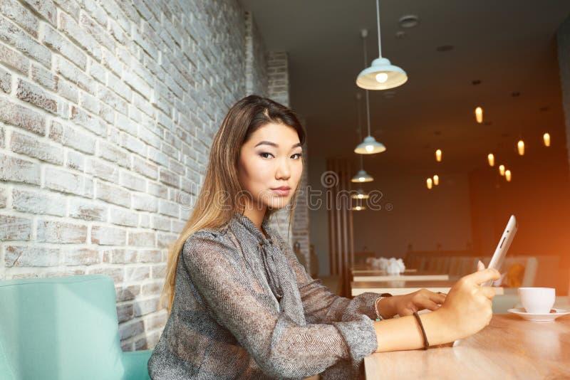 Γοητευτικός τη νέα γυναίκα έχει την τηλεοπτική συνομιλία ενώ πρόγευμα στη καφετερία στοκ εικόνες